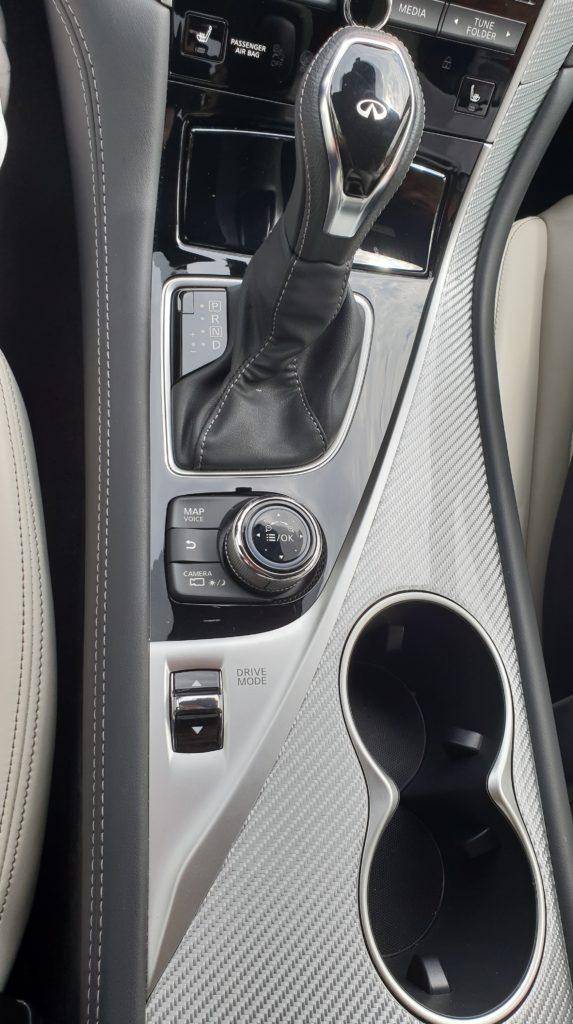 Stredový panel Infinity Q60 s ovládačmi infotainmentu a jazdných režimov
